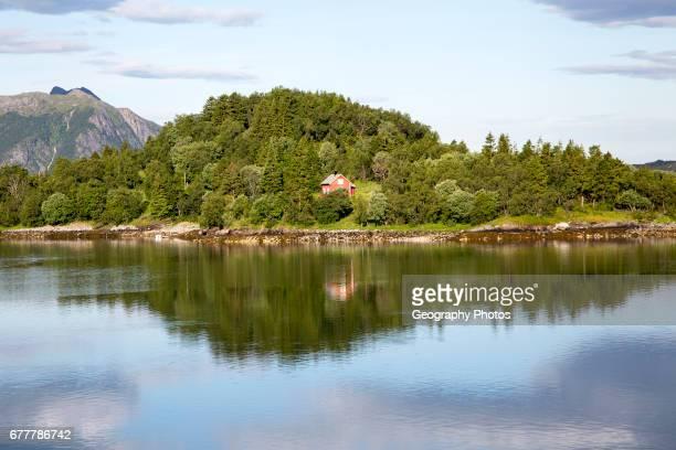 Isolated coastal house on small wooded island near Ornes, Nordland, Norway.
