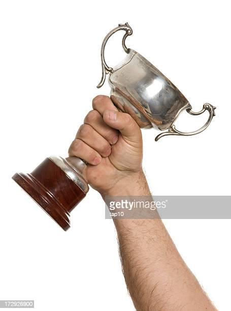Isolated image of a fist holding a silver cup trophy