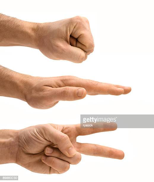 isolated male hands symbolizing rock paper scissors on white - scissors stock pictures, royalty-free photos & images