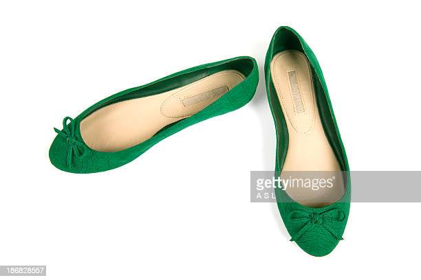 Isolated pair of green flat shoes with bow