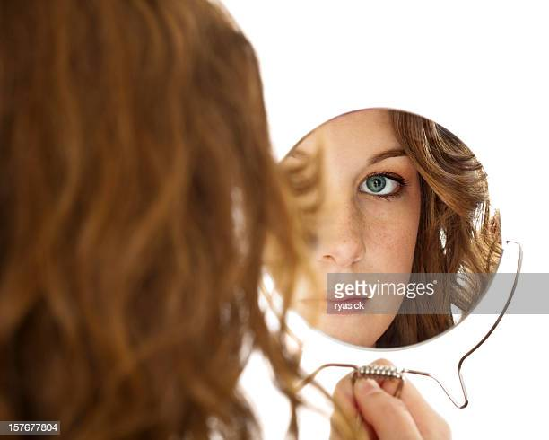 Isolated Reflection of Female Brunette Teen Gazing Into Handheld Mirror
