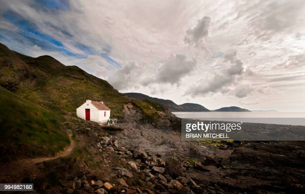isolated sea side cottage with sweeping sea view - isle of man stock pictures, royalty-free photos & images
