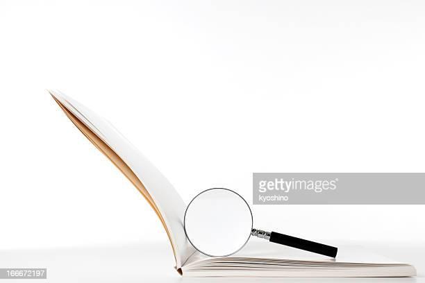 Isolierte Schuss von leere Buch mit Lupe auf Weiß