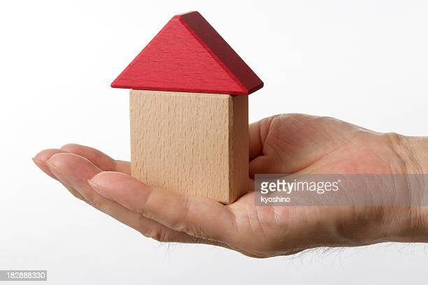 Isolated shot of block home in hand against white background