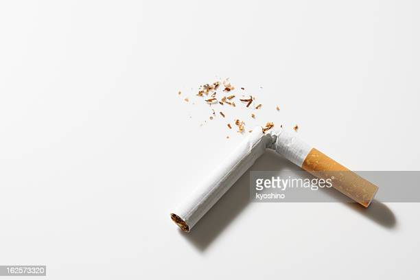 isolated shot of broken cigarette on white background - cigarette stock pictures, royalty-free photos & images