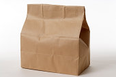 Isolated shot of closed brown paper bag on white background