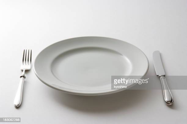 Isolated shot of empty plate and cutlery on white background