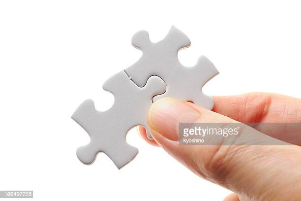 isolated shot of holding a jigsaw puzzle on white background - puzzle pieces stock pictures, royalty-free photos & images
