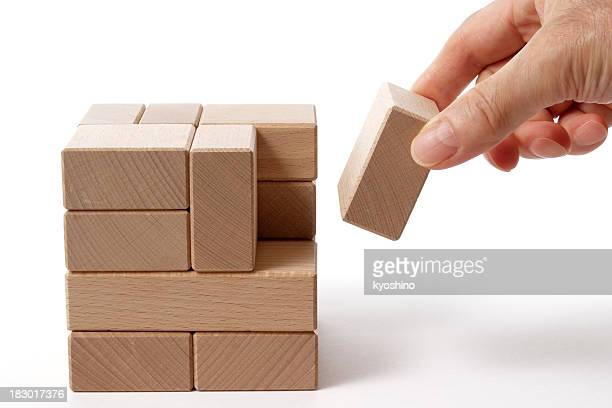 Isolated shot of holding a wood block on white background