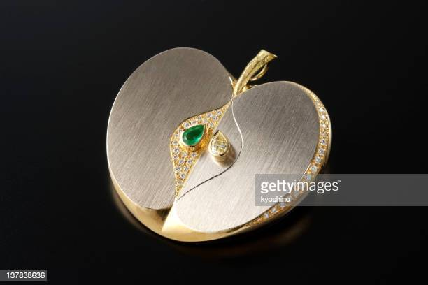 Isolated shot of luxury gold apple brooch on black background