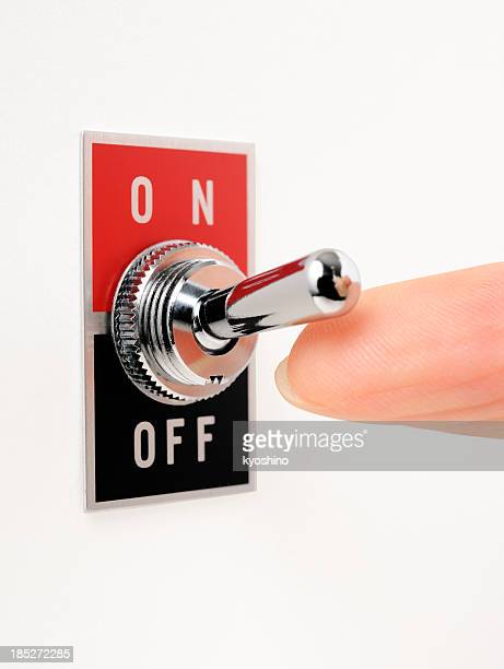 Isolated shot of ON/OFF switch with finger on white background
