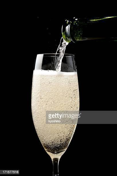 Isolierte Schuss von gießen Champagner auf schwarzem Hintergrund