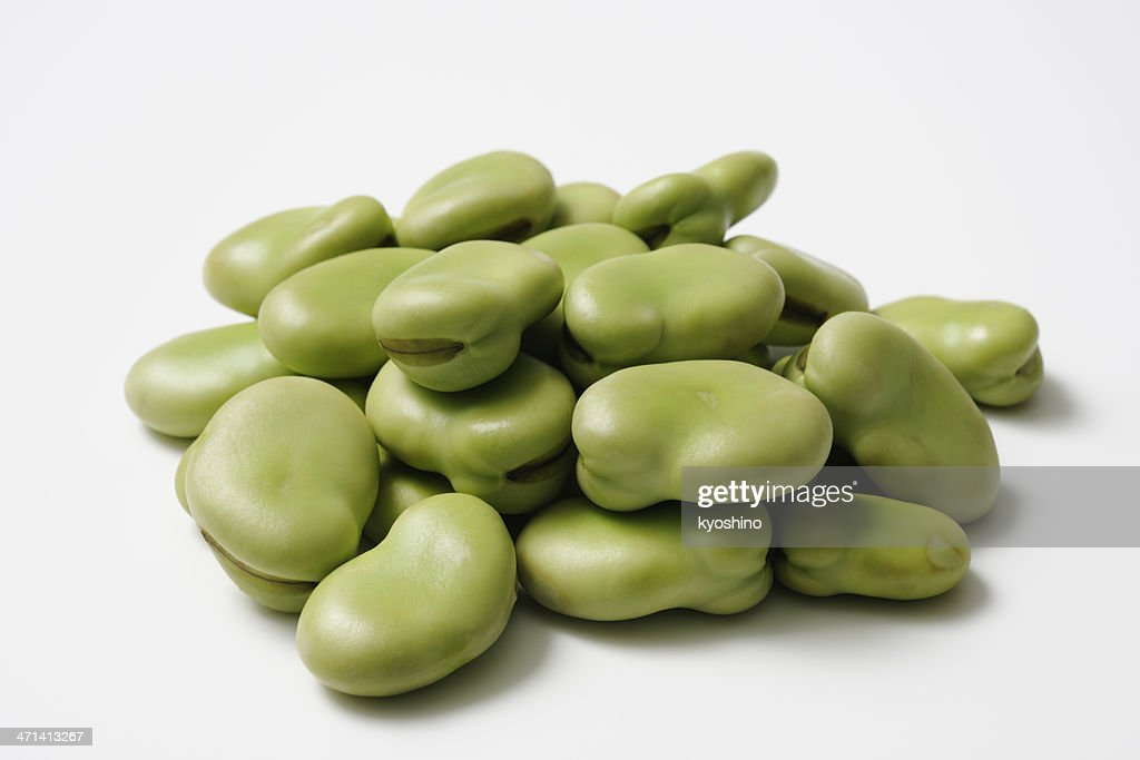 Isolated shot of stacked uncooked broad beans on white background : Stock Photo