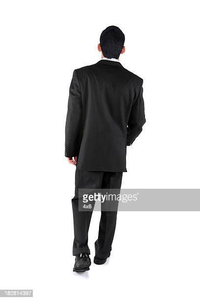 Isolated young businessman walking away