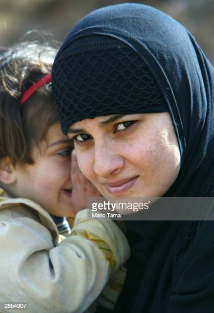 Isra Shakir and her daughter Shirooq wait outside Abu Ghraib prison in the hopes that Isra's husband will be among those released under an announced...