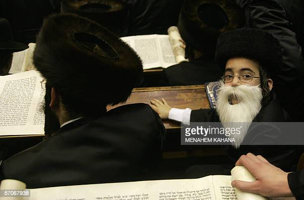A boy looks over as Ultra Orthodox Jews from the Wiznitz Hassidim group reads the Ester scrolls at the synagogue in the Israeli town of Beni Brak...