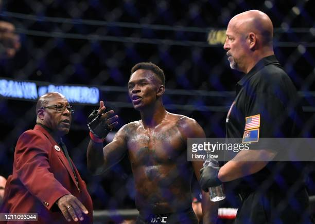 Israel Adesanya argues with Yoel Romero's corner after his decision win during a middleweight title bout at TMobile Arena on March 07 2020 in Las...