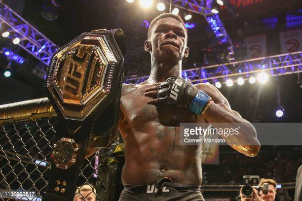 Israel Adesanya holds up the belt after defeating Kelvin Gastelum by unanimous decision in their interim middleweight championship bout during the...