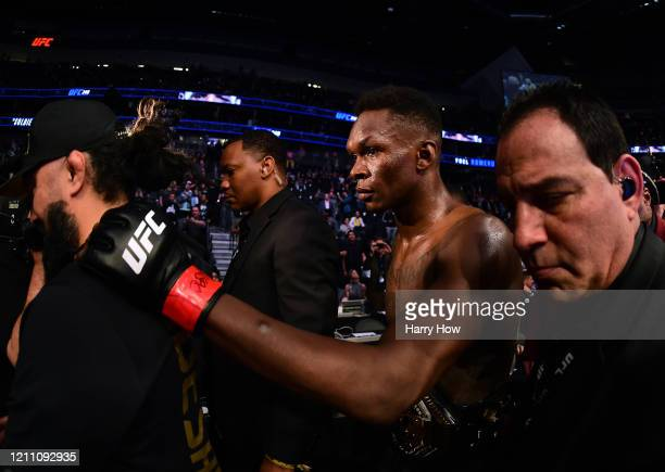 Israel Adesanya is escorted out of the ring after a decision win over Yoel Romero during a middleweight title bout at TMobile Arena on March 07 2020...