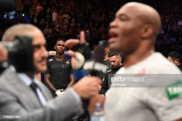 Israel Adesanya of New Zealand looks on as Anderson Silva of Brazil is interviewed after their middleweight bout during the UFC 234 at Rod Laver...