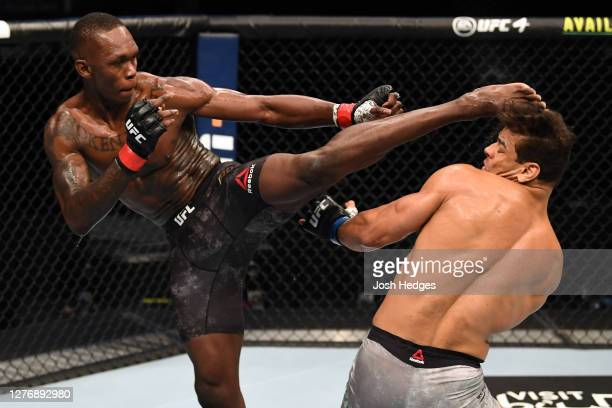 Israel Adesanya of Nigeria kicks the head of Paulo Costa of Brazil in their middleweight championship bout during UFC 253 inside Flash Forum on UFC...