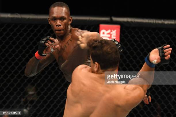 Israel Adesanya of Nigeria lands a head kick to Paulo Costa of Brazil in their middleweight championship bout during UFC 253 inside Flash Forum on...
