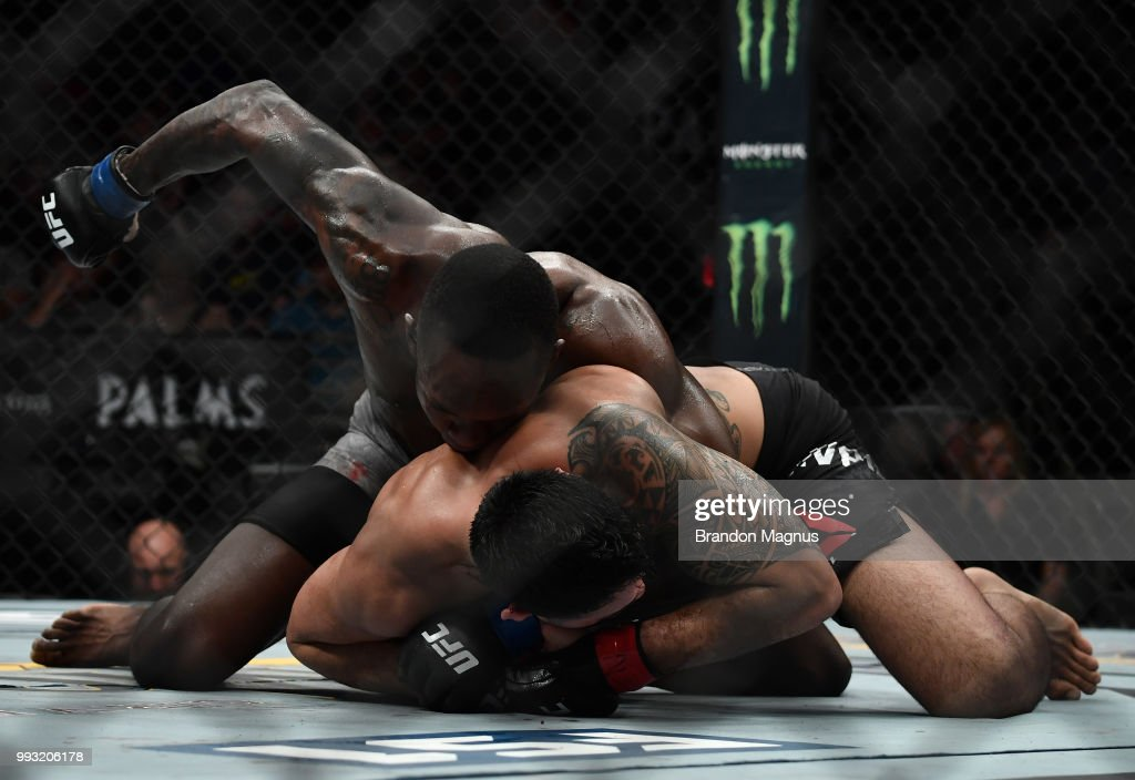 Israel Adesanya of Nigeria (top) punches Brad Tavares in their middleweight bout during The Ultimate Fighter Finale event inside The Pearl concert theater at Palms Casino Resort on July 6, 2018 in Las Vegas, Nevada.