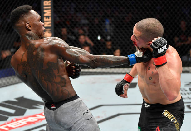 Israel Adesanya of Nigeria punches Robert Whittaker of New Zealand in their UFC middleweight championship fight during the UFC 243 event at Marvel...