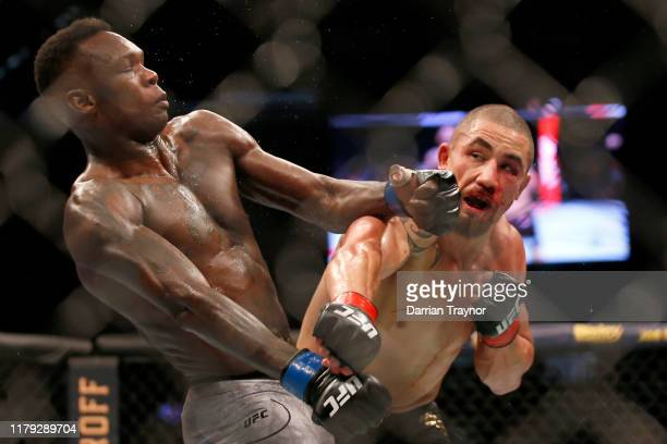 Israel Adesanya punches Robert Whittaker between in their Middleweight title bout during UFC 243 at Marvel Stadium on October 06 2019 in Melbourne...