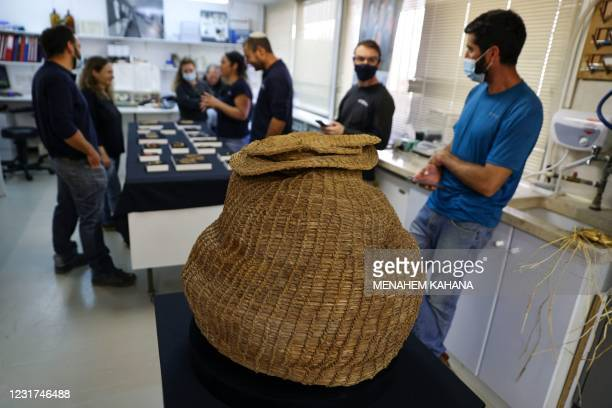 Israel Antiquities Authority archaeologists stand next to a 10500-year-old basket dating back to the Neolithic period that was unearthed in Murabaat...