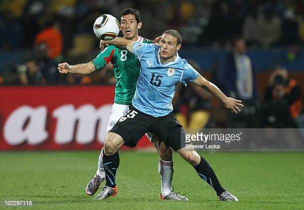 Israel Castro of Mexico and Diego Perez of Uruguay battle for the ball during the 2010 FIFA World Cup South Africa Group A match between Mexico and...