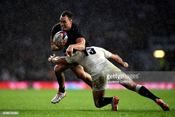 Israel Dagg of New Zealand is tackled by Brad Barritt of England during the QBE International match between England and New Zealand at Twickenham...