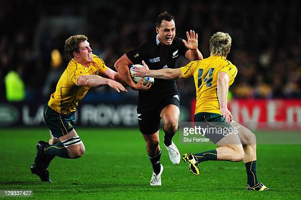 Israel Dagg of the All Blacks evades the tackle of David Pocock and James O'Connor of the Wallabies during semi final two of the 2011 IRB Rugby World...