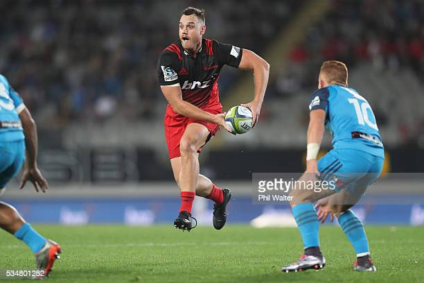 Israel Dagg of the Crusaders looks for support under pressure from Ihaia West of the Blues during the round 14 Super Rugby match between the Blues...