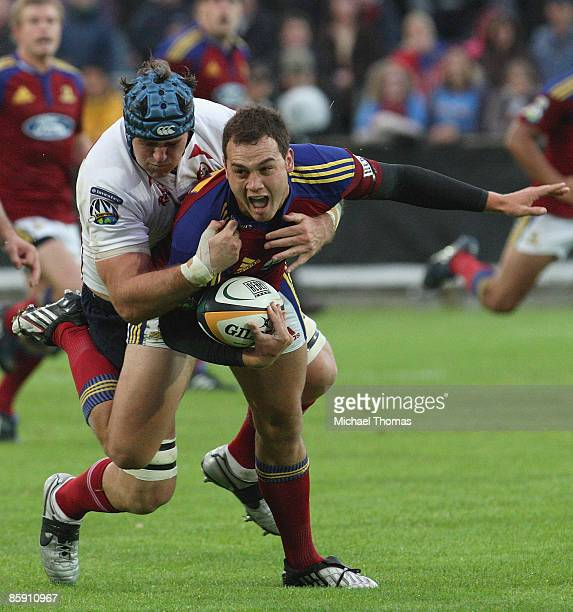 Israel Dagg of the Highlanders is tackled by James Horwill of the Reds during the round nine Super 14 match between the Highlanders and the Reds at...