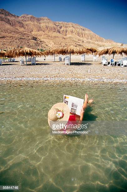 Israel, Dead Sea, Rear view of a woman floating on water and reading a newspaper