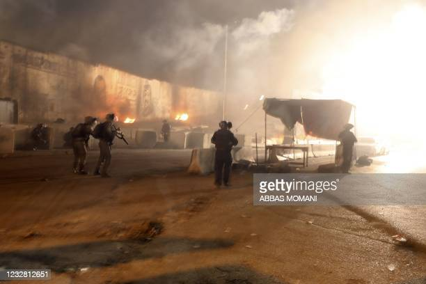 Israel Defense Forces soldiers throw tear gas canisters at Palestinian demonstrators during an anti-Israel demonstration over tensions in Jerusalem,...