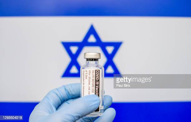 israel flag with coronavirus covid-19 concept. doctor with blue protection medical gloves holds a vaccine bottle. coronavirus covid 19 vaccine research - israel stock pictures, royalty-free photos & images