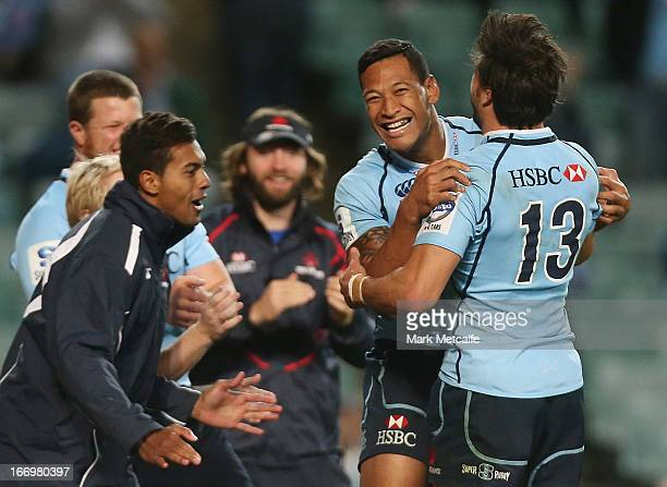 Israel Folau cof the Waratahs celebrates scoring a try with teammate Adam AshleyCooper during the round 10 Super Rugby match between the Waratahs and...