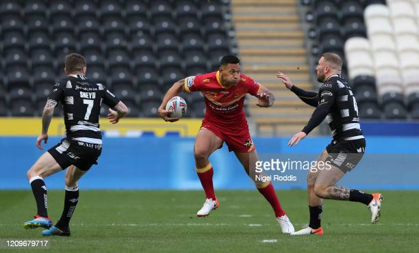 Israel Folau of Catalan Dragons goes into contact with Marc Sneyd and Jake Connor of Hull FC during the Betfred Super League match between Hull FC...