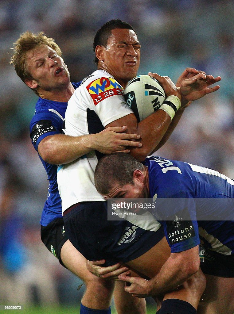 Israel Folau of the Broncos is tackled by David Stagg and Andrew Ryan of the Bulldogs during the round seven NRL match between the Canterbury Bulldogs and the Brisbane Broncos at ANZ Stadium on April 23, 2010 in Sydney, Australia.