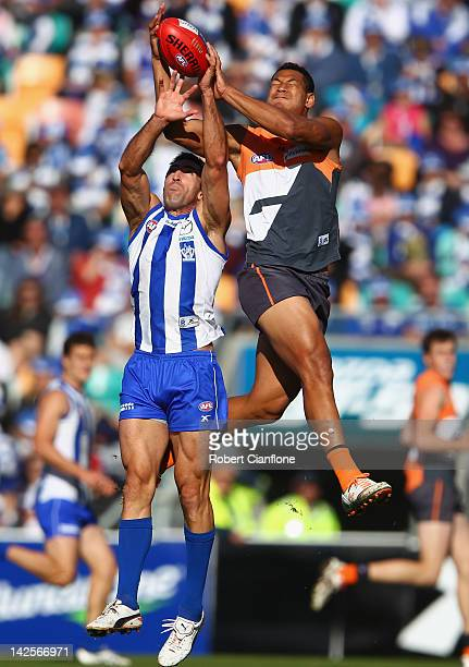 Israel Folau of the Giants attempts to mark over Michael Firrito of the Kangaroos during the round two AFL match between the North Melbourne...
