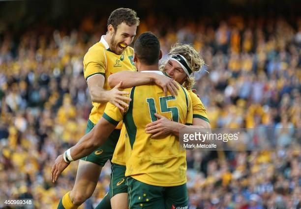 Israel Folau of the Wallabies celebrates scoring a try with team mates Nic White and Michael Hooper during the International Test match between the...