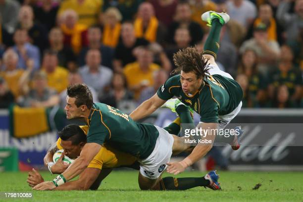 Israel Folau of the Wallabies is tackled by JJ Engelbrecht and Zane Kirchner of the Springboks during The Rugby Championship match between the...