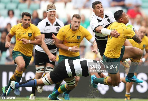 Israel Folau of the Wallabies is tackled by Tim NanaiWilliams of the Barbarians during the match between the Australian Wallabies and the Barbarians...