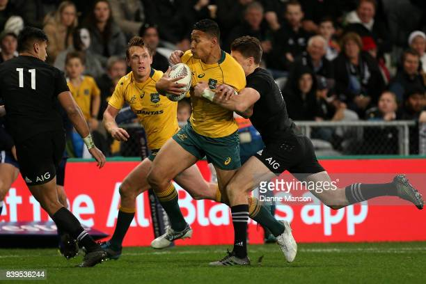 Israel Folau of the Wallabies tries to break the tackle of Beauden Barrett of the All Blacks during The Rugby Championship Bledisloe Cup match...