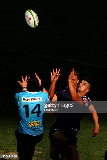 Israel Folau of the Waratahs and Jack Maddocks of the Rebels compete for the ball from a kick during the round five Super Rugby match between the...