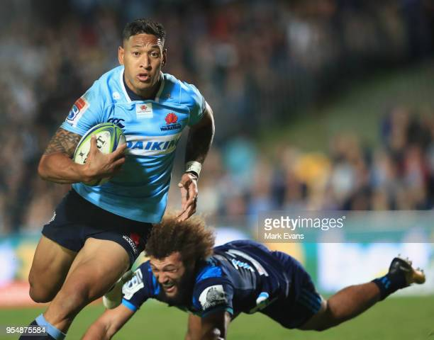Israel Folau of the Waratahs breaks free from the tackle of Ross Wright of the Orbyn Leger of the Blues during the round 12 Super Rugby match between...
