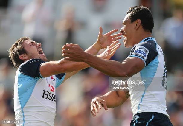 Israel Folau of the Waratahs celebrates with Brendan McKibbin after scoring the first try of the game during the Super Rugby trial match between the...