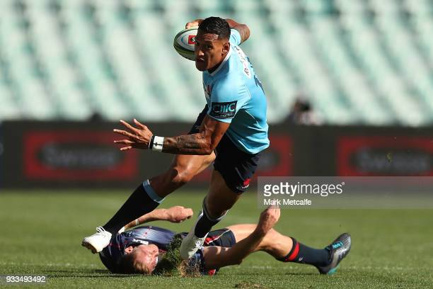 Israel Folau of the Waratahs evades the tackle of Reece Hodge of the Rebels during the round five Super Rugby match between the Waratahs and the...